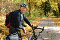 a cyclist in the autumn forest, a man with a Bicycle in black clothes