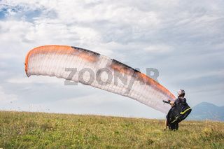 The paraglider opens his parachute before taking off from the mountain in the North Caucasus. Filling the parachute wing with air before takeoff