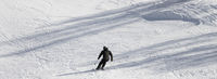 Skier on ski slope at sun winter day