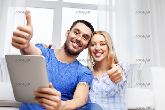 couple with tablet computer showing thumbs up