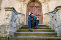 Portrait of a young man sitting against a beautiful old medieval cathedral door. A man in front of a an old architecture church entrance door in Alba Iulia, Romania