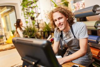 Junger Mann als Florist an der Computer Kasse