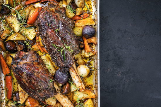Venison knuckle with fried potatoes and vegetable as top view in a casserole with copy space right