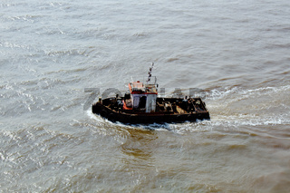 small tug boat swings in the waves