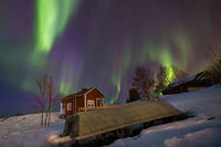 Polar lights over a cabin and rowing boat in the snow in Inari, Finland