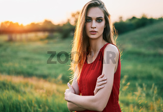 Portrait of beautiful confident young woman with crossed arms posing outdoors