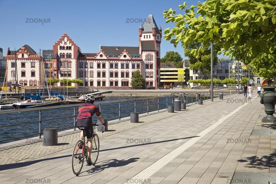 Cyclist with castle Hoerde at Phoenix Lake, Dortmund, North Rhine-Westphalia, Germany, Europe