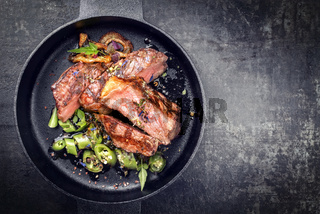 Modern Style classic dry aged sliced roast beef with fried onion rings and chili served as top view in a minimalistic design cast-iron skillet with copy space right