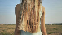 A young blonde girl stands with her back demonstrating her long hair.