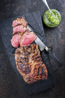 Barbecue Argentinian dry aged wagyu tri tip steak with chimichurri sauce as dip as top view on a carbonized wooden board