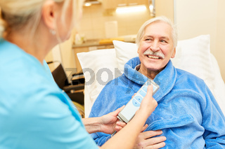 Pflegekraft mit Fernbedienung am Pflegebett