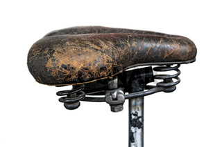 The leather saddle on old motorcycle, isolated on white background. The Hildebrand Wolfmuller (1894), first series produced motorcycle in the world.