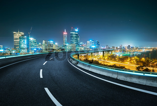 Blue neon light design highway overpass with modern city background . Night scene .