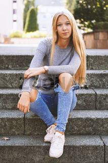 teenage girl sitting on steps outside