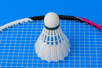 Badminton shuttlecock and racket on blue background