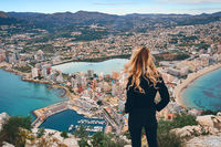 Rear view woman climbed up on peak of Penon de Ifach rock enjoy picturesque view Mediterranean Sea, mountain range, cityscape scenery. Tourism, famous beautiful place visit hiking concept. Calpe Spain