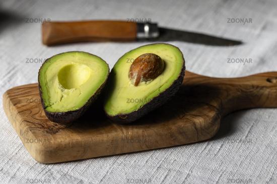 Halves of avocado on a board