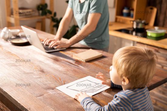Little boy typing on drawn laptop