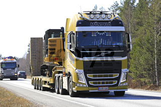 Yellow Volvo FH Semi Trailer Hauls Excavator