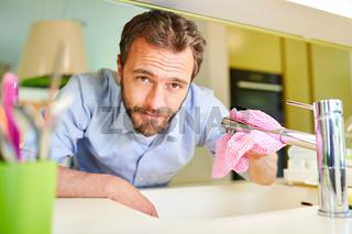 Hausmann mit Lappen beim Armatur putzen