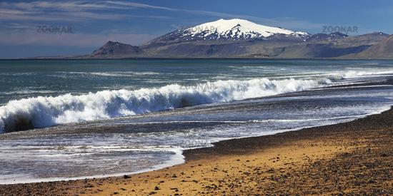 Beach with surf, behind snow covered volcano and glacier Snæfellsjökull, Snæfellsnes, Iceland Europe