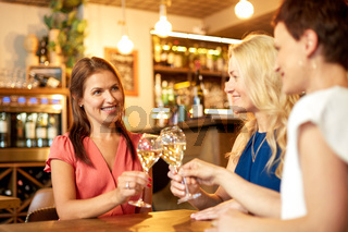 happy women drinking wine at bar or restaurant