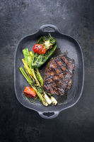 Barbecue dry aged wagyu entrecote beef steak with vegetable and herbs as top view on a gray cast iron pan with copy space
