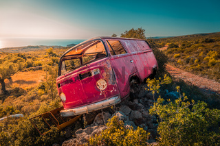 Abandoned van bus on the rocks in the middle of nowhere on a sunny day. Sea in the background.