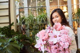 Floristin bei der Lieferung von rosa Blumenstrauß