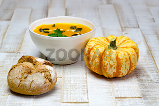 organic pumpkin soup in a white bowl framed by pumpkin and chestnut bread