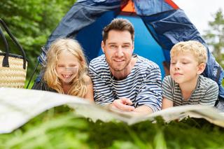 Vater und zwei Kinder beim Camping
