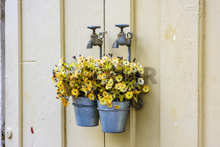 Bucket with flowers hanging on an old faucet