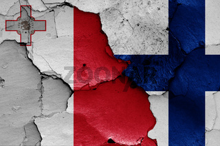 flags of Malta and Finland painted on cracked wall