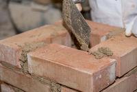 Craftsman builds brick wall with small bricks - Close-up masons
