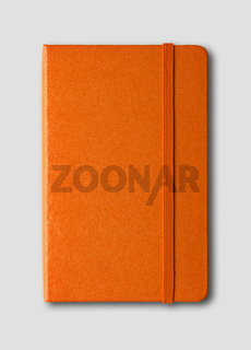 Orange closed notebook isolated on grey