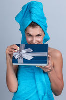 Woman with towel on head open gift box