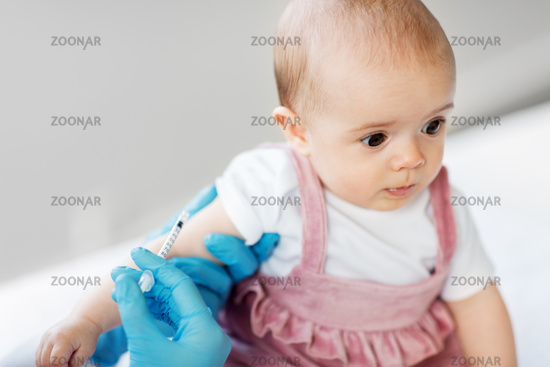 doctor making vaccine for baby patient at clinic