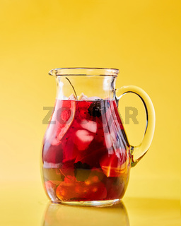 Fruit berry homemade lemonade in a glass jug on a yellow background with copy space. Healthy drink
