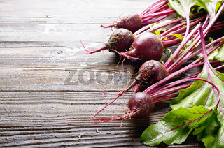 Fresh organic beetroots on kitchen wooden rustic table close up view. Space for text