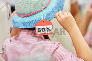 Mädchen in der Anprobe beim Hut Kauf