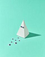White plastic pyramid with eyes as Halloween simbol.