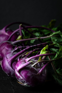 Purple kohlrabi. Shooting on a black background in a low key close-up.