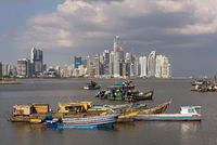 old wooden fishing boats in front of the skyline of panama city panama