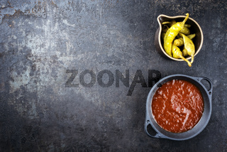 Traditional barbecue ingredients with hot sauce and peperoni as top view on an old metal board with copy space left