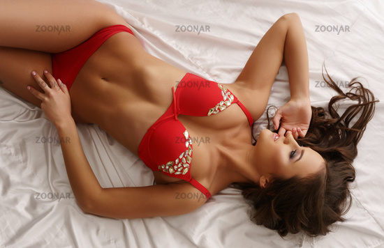 Top view of sensual lingerie model lying in bed