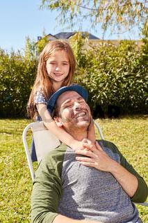 Tochter umarmt Vater auf einem Stuhl im Garten