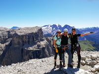 mountain guide and two female climbers celebrate standing on the summit after a climb