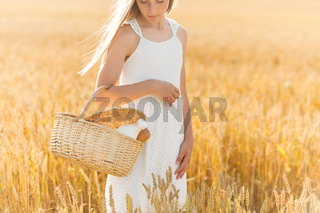 girl with bread and milk in basket on cereal field