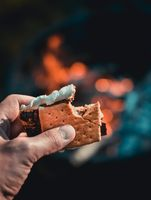 Having a s'more over the fire in the summer
