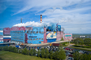 Summer industrial landscape - Arkhangelsk Pulp and Paper Mill, central watch, white smoke from the pipes against the blue sky, editorial photo